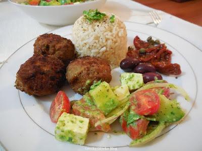na talerzu: kotelty mielone, kopiec białego ryżu, grecka sałatka, oliwki, kapary