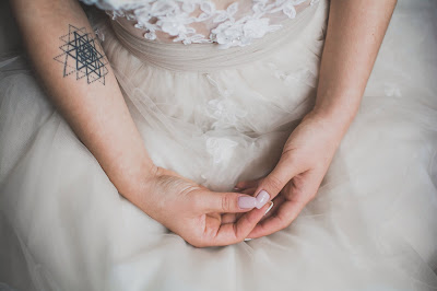Close up on a bride's hands and white dress detail