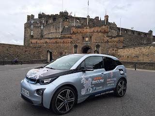 BMW i3 electric car with range extender petrol engine parked in front of Edinburgh castle