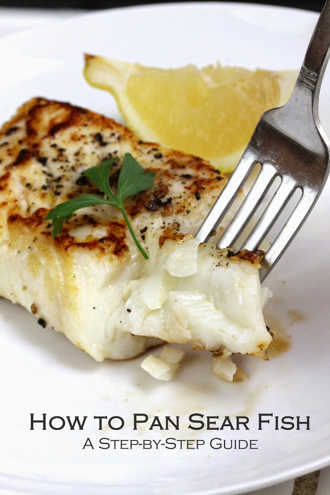 How to Pan Sear Fish, A Step-By-Step Guide - A fork lifts a bite of pan seared fish. Fish is garnished with a sprig of parsley and a lemon wedge.
