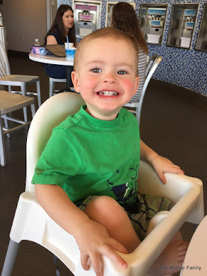 Benjamin sitting in a high chair and smiling a big toothy grin