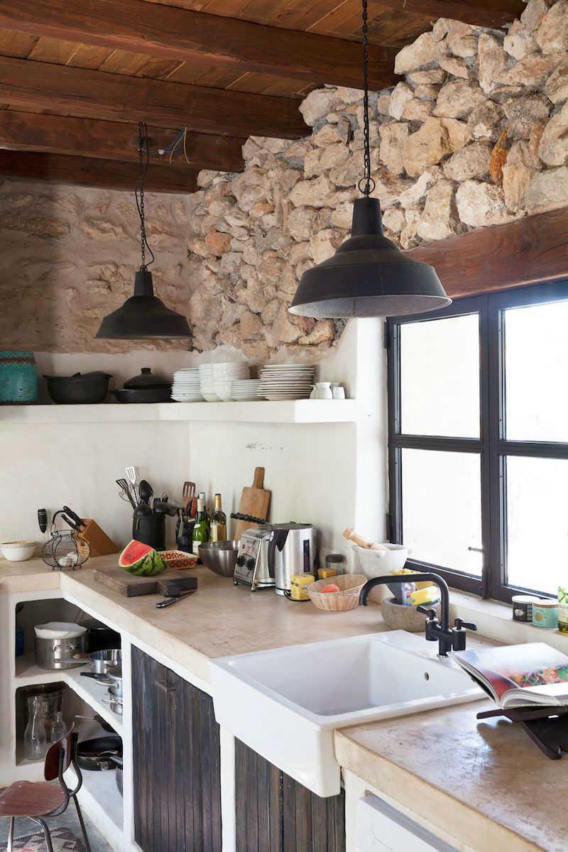 Cocina con pared de piedra y azulejos.