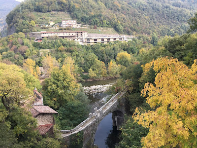 The stone bridge of Clanezzo (Ponte di Attone), at one time a point for collecting customs. The bridge allows passage over the Imagna River. In the background, the Brembo River.