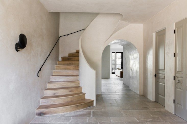Beautiful sculptural staircase in villa with European inspired interiors by Leigh Herzig - seen on Hello Lovely