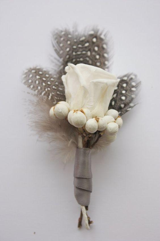 Un boutonniere con plumas de estilo vintage en tonos pardos y blanco, perfecto para invierno