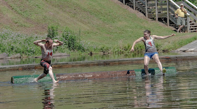 A man and a woman compete in a log rolling contest in sawmill pond at PA Lumber Museum