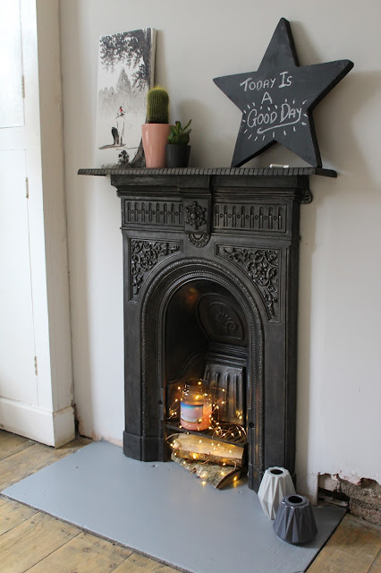 victorian fireplace with logs and fairy lights