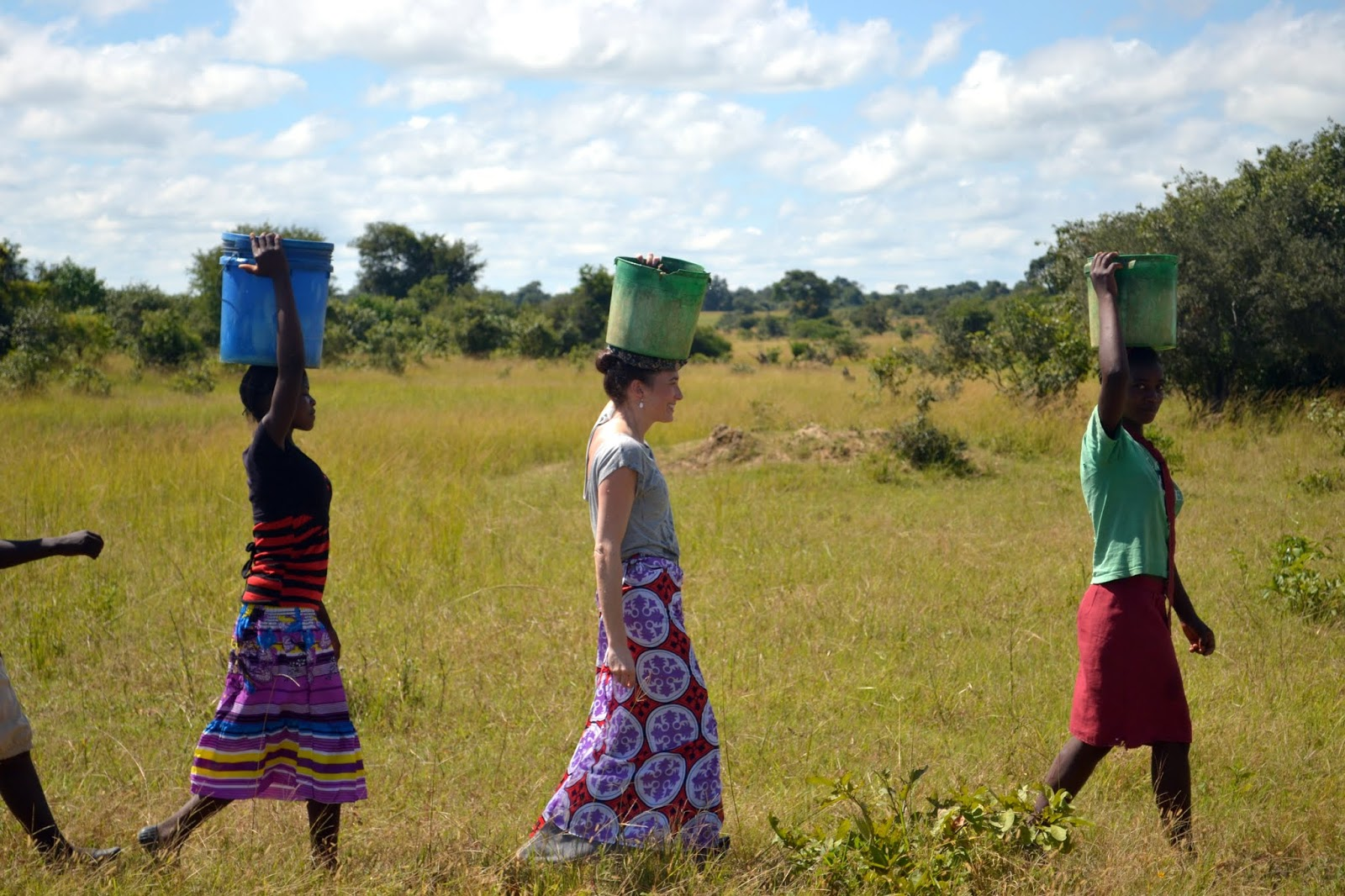 carrying water buckets on head in africa