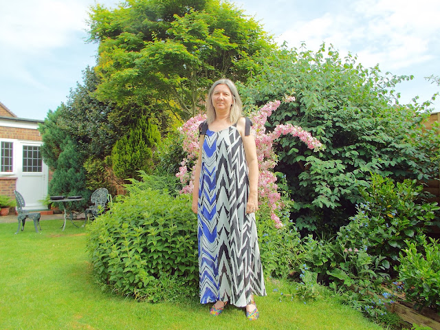 Navy and black zig zag dress  from JD Williams website modelled in a green and leafy garden