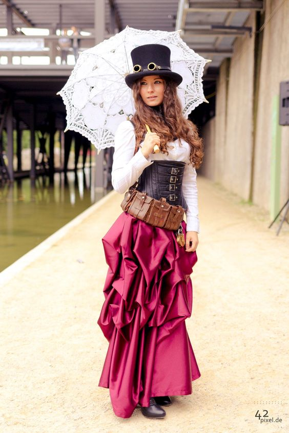 Steampunk girl wearing a magenta red/pink silk skirt, what lace parasol, black corset, white blouse, black top hat and goggles