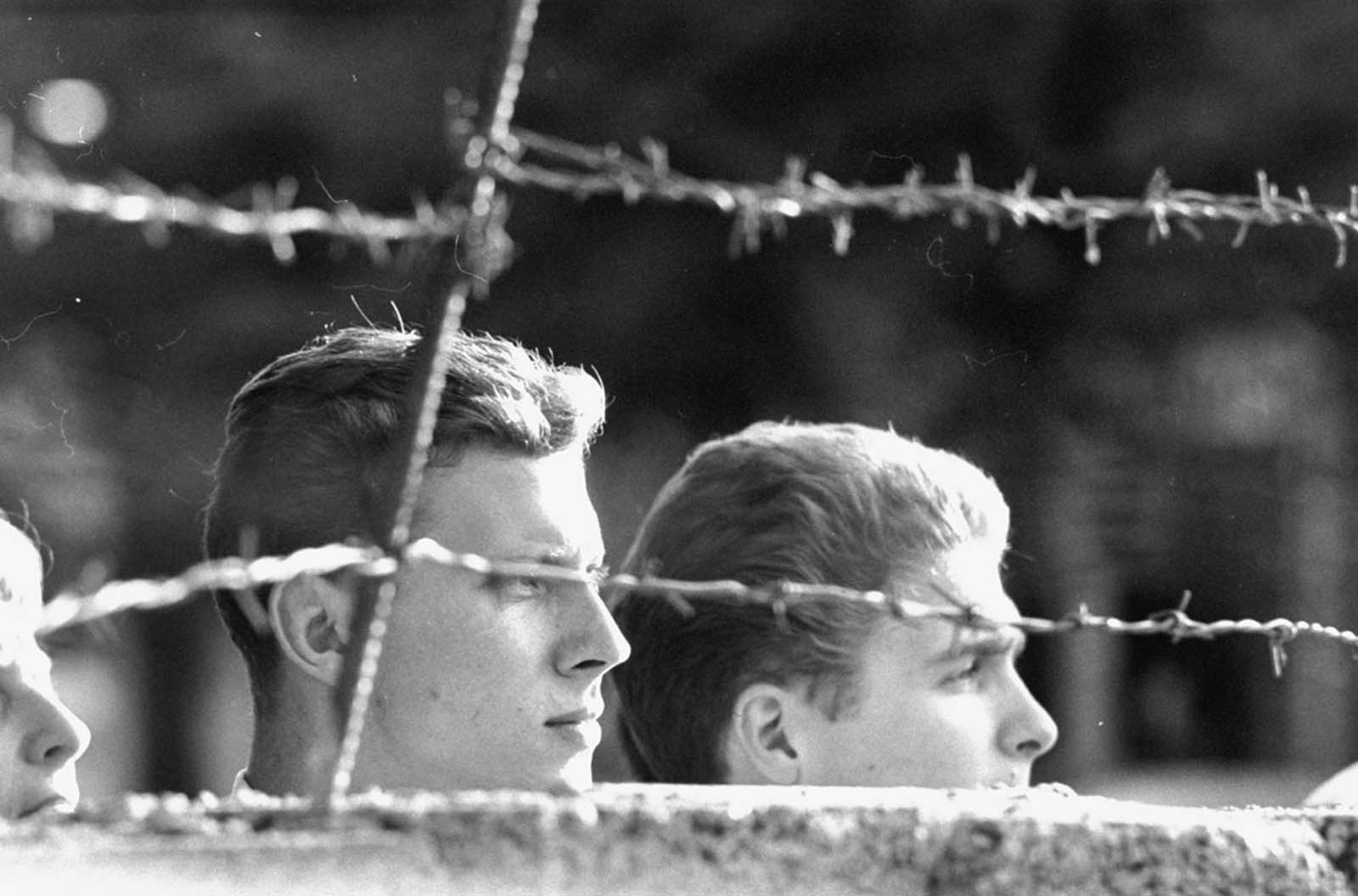 West Germans peer over part of the newly constructed Berlin Wall while waiting for relatives to return from the eastern sector in August 1961.