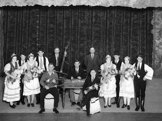 Imagen en blanco y negro de un grupo real de músicos, bailarines y bailarinas húngaros en un teatro