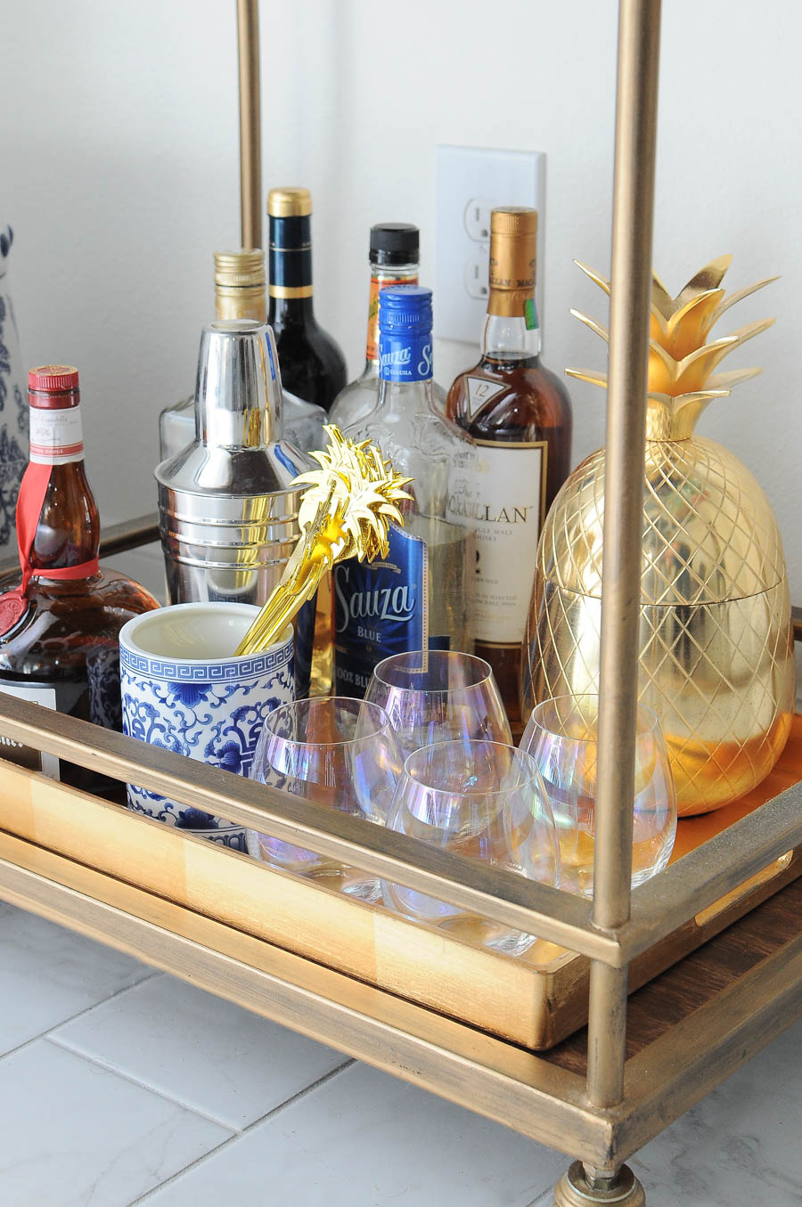 Spring bar cart decor styling ideas- florals, candles, liquor, and lots of chic and glam accents.