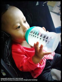 gambar bayi Nor Aina sedang minum susu botol sambil menunggu doktor memeriksanya.