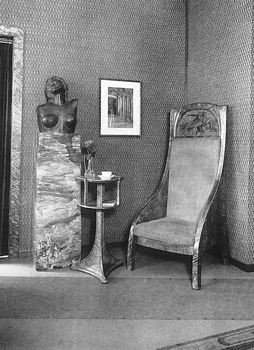 photograph of a 1905 interior with upholstered stone furniture,  from an exposition in Germany?