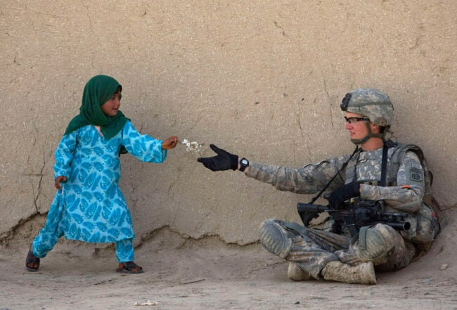 16 Pictures Of Children Restored Our Faith In Humanity - An Afghan girl gives flowers to a US Army soldier during a patrol in the Arghandab Valley in Afghanistan.
