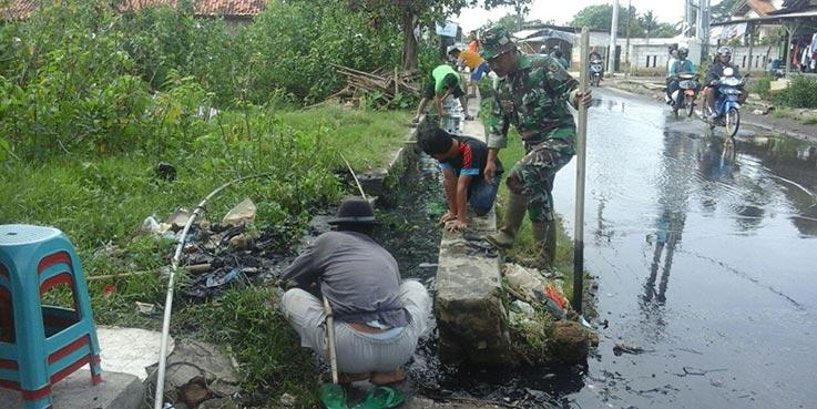 Mereka yang sedang membersihkan saluran air dari sampah dan lumpur.
