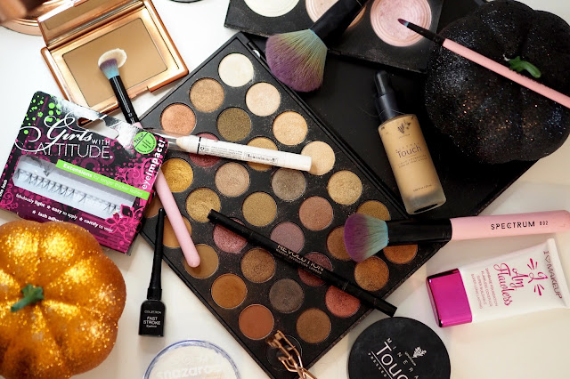 a collection of makeup used including a gold/brown makeup palette, brushes, eyelashes, bronzer, eyeliner and a glittery pumpkin for decoration