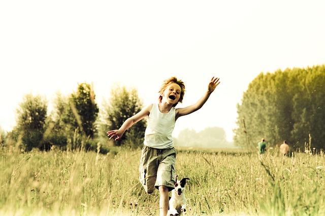 Fröhlicher Junge läuft hinter Hund her