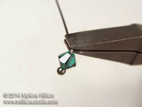 Head pin bent at a right angle above an emerald Swarovski bicone crystal.