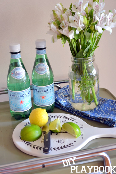 Flowers, cutting lemons and limes, and pellegrino add more to the bar cart.
