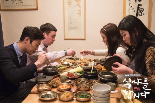 vemos decenas de platos en la mesa, tres de los protagonistas sirviendose y el cocinero australiano pero especializado en cocina coreana sentado con ellos.