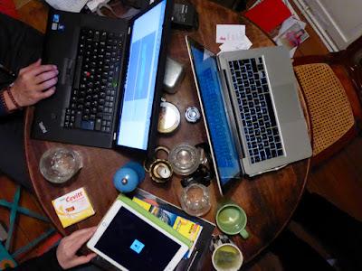 Hände, zwei Computer, ein Tablet, Wassergläser, Teebecher, Pfeffermühle, Salz, Kerze, Vitamine, Visitenkarten, Stühle (angeschnitten), Kataloge auf Bank und Boden