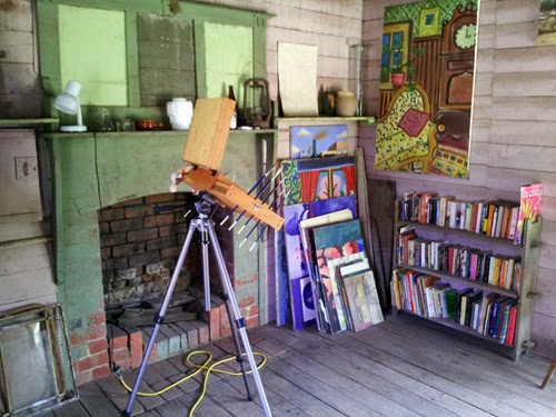Photograph of a slightly dilapidated room set up as an art studio and featuring a pochade box on a tripod, a fireplace and a small bookshelf full of books.