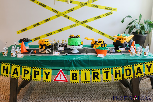 Construction Party tablescape with Caution tape, trucks, cones, and construction themed snacks