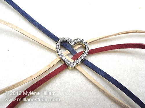 The Cranberry lace is threaded over and under the Cadet Blue and Sand Beach laces, parallel to the 2nd Sandy Beach lace.