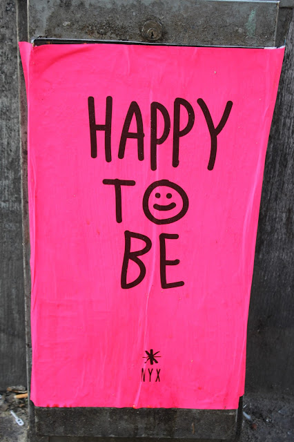 """A bit of Amsterdam street art - an illustration that reads """"Happy to be""""."""