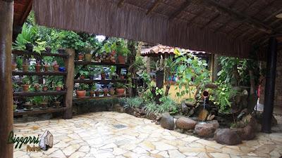 Detalhe da execução do paisagismo com as pranchas de madeira com os vasos de barro, os canteiros de pedra com plantas, o laguinho de carpas com pedra do rio com a bica d'água no pote de barro e o piso de pedra caco de São Tomé.
