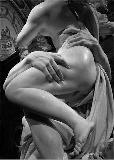 Gian Lorenzo Bernini ou simplesmente Bernini (Nápoles, 7 de dezembro de 1598 – Roma, 28 de novembro de 1680) foi um eminente artista do barroco italiano, trabalhando principalmente na cidade de Roma. Distinguiu-se como escultor e arquiteto, ainda que tivesse sido pintor, desenhista, cenógrafo e criador de espectáculos de pirotecnia. Esculpiu numerosas obras de arte presentes até os dias atuais em Roma e no Vaticano.Descrição: Foto em preto e branco de parte de uma escultura em mármore: O rapto de Proserpina. O deus Hades sustenta a deusa Proserpina na altura dos ombros, nua, com o corpo em perfil ; a perna esquerda pousa levemente sobre a outra e produz sombra no joelho direito; o delicado pé esquerdo, voltado para baixo está no ar. A mão direita de Hades segura fortemente a coxa de Proserpina, os dedos pressionam a carne de aspecto firme; a outra mão de Hades enlaça vigorosamente a cintura da deusa, o dedo indicador afunda na carne lateral das costas e forma um L com o dedo polegar. No topo, parte das pontas dos cabelos cacheados de Proserpina ao vento, nas costas, uma sombra contrasta o brilho de um foco de luz sobre o ombro e, parte do braço em angulo, revela uma porção do pequeno seio esquerdo próximo aos cabelos ondulados de Hades; a mão da deusa se lança a frente do corpo e atinge a cabeça de Hades. Entre os corpos vigorosos, um manto ondula em pregas. No teto, uma pintura com duas figuras humanas.