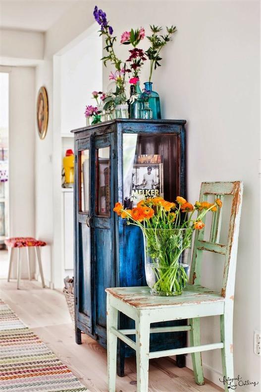 botellas y jarrones de cristal de colores con flores sobre alacena antigua chicanddeco