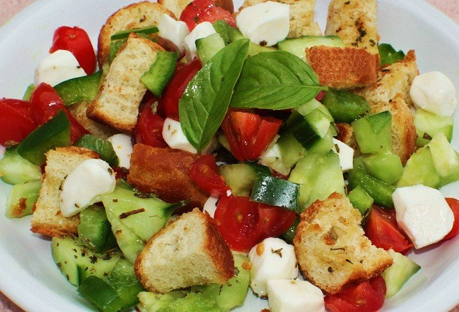 this is a salad in a white plate with  fresh basil, cucumbers, cubed mozzarella, toasted bread cubes and tomatoes all fresh