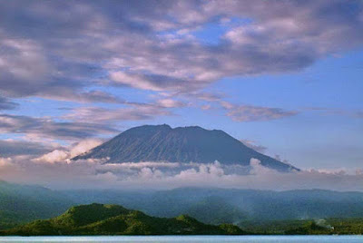 """Sejarah Gunung Agung di Bali              Saat gunung Merapi di Jogja meletus, Indonesia geger dan terenyuh dengan meninggalnya Mbah Marijan sang juru kunci gunung Merapi tersebut, tapi kalau kita lihat saat tahun 1963 gunung Agung meletus di Bali, tak hanya juru kunci gunung Agung nya yang tak mau mengungsi, bahkan hampir semua lelaki dewasa dari beberapa desa """"menyambut"""" lahar tumpahan gunung Agung tersebut…sedikit kronologis dan kisahnya….   Gunung Agung merupakan sebuah gunung vulkanik tipe monoconic strato yang tingginya mencapai sekitar 3.142 meter di atas permukaan laut. Gunung tertinggi di Bali ini termasuk muda dan terakhir meletus pada tahun 1963 setelah mengalami tidur panjang selama 120 tahun. Sejarah aktivitas Gunung berapi Agung memang tidak terlalu banyak diketahui.   Catatan sejarah mengenai letusan gunung ini mulai muncul pada tahun 1808. Ketika itu letusan disertai dengan uap dan abu vulkanik terjadi. Aktivitas gunung ini berlanjut pada tahun 1821, namun tidak ada catatan mengenai hal tersebut. Pada tahun 1843, Gunung Agung meletus kembali yang didahului dengan sejumlah gempa bumi. Letusan ini juga menghasilkan abu vulkanik, pasir, dan batu apung. Sejak 120 tahun tersebut, baru pada tahun 1963 Gunung Agung meletus kembali dan menghasilkan akibat yang sangat merusak"""