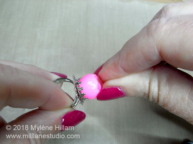Pressing the bead firmly into the filigree ring base.