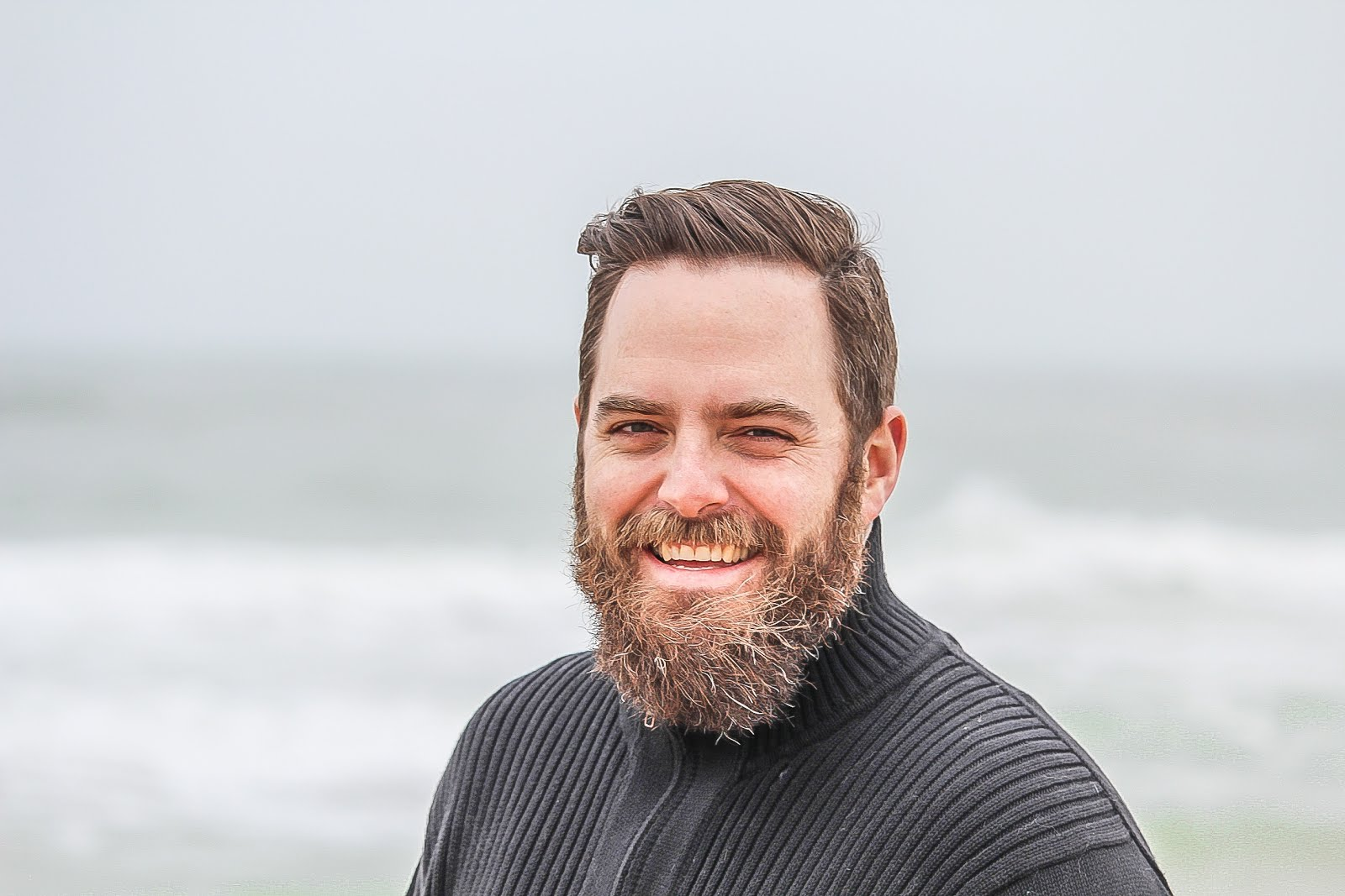 man wearing black zip up jacket near beach smiling at the photo
