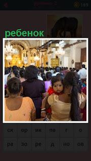 в помещении церкви на руках женщины находится ребенок