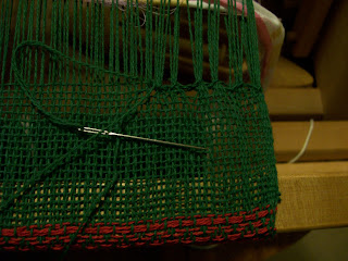 Finishing the woven cloth with hem-stitch.