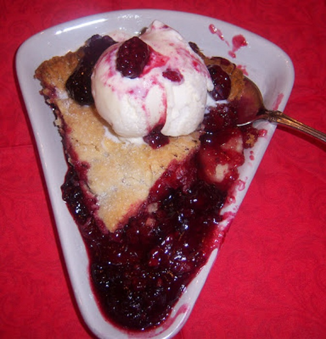 red raspberry pie with a scoop of vanilla ice cream on top in a pie shaped plate and spoon