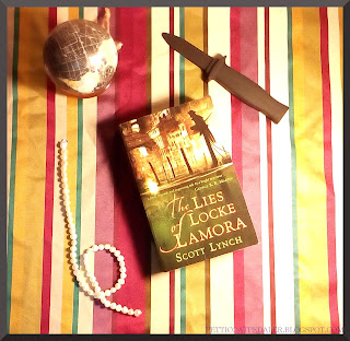 "A copy of the book ""The Lies of Locke Lamora"" sitting on a warm colored striped fabric with a small black knife, a globe, and a string of pearls."