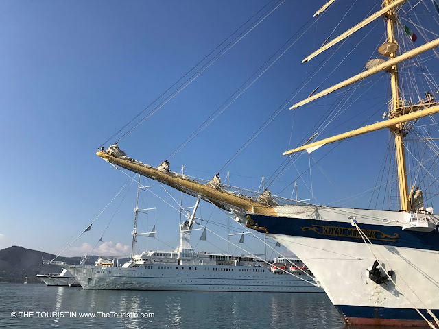 A tall ship next to a cruise ship under a bright blue sky.