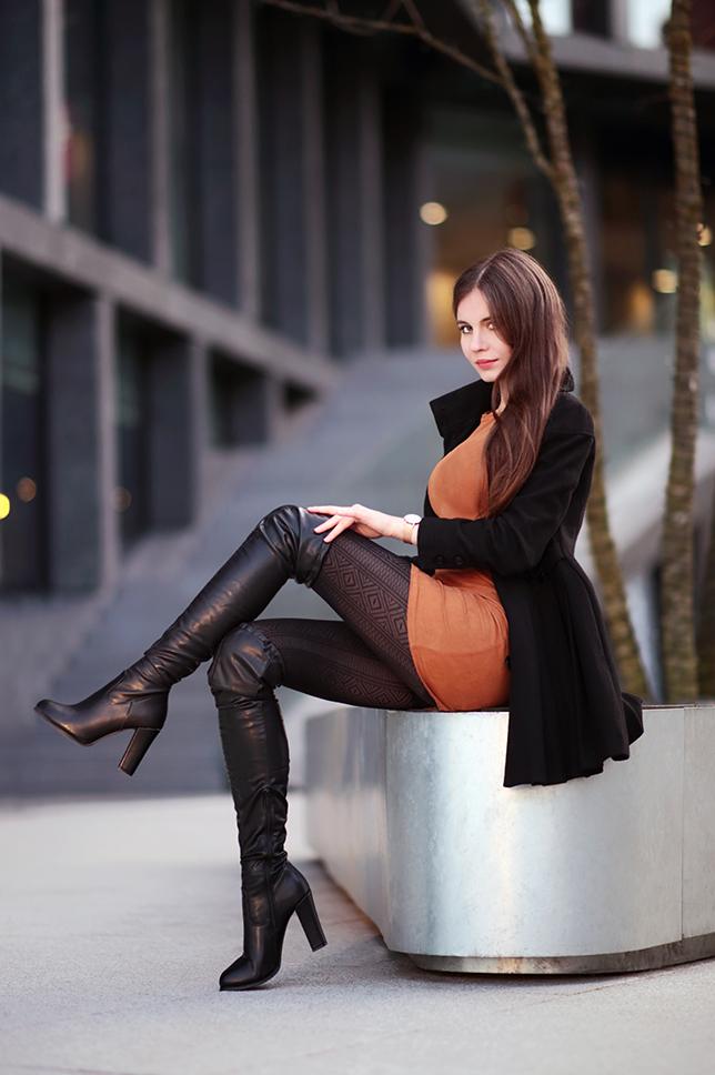 Brązowa sukienka, czarny płaszcz, wzorzyste rajstopy i ...