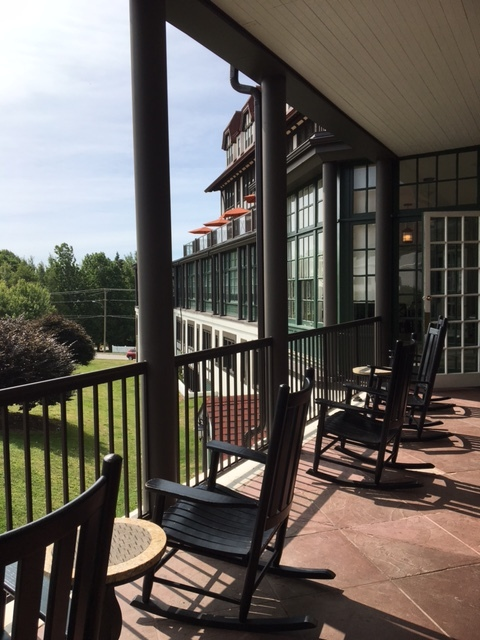 a veranda of a hotel with several rocking chairs