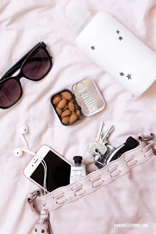 Flatlay rosa Tasche mit Mandeln, bkr Flasche, Handy, Sonnenbrille