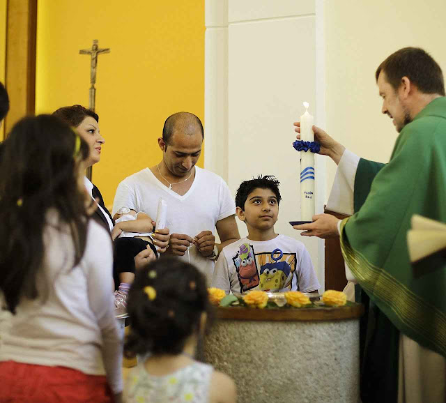 O Pe Gottfried Martens batiza família iraniana em Berlim. Ex-muçulmanos constituem maioria dos 900 paroquianos.