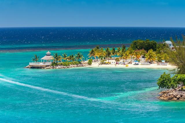 Plage d'Ocho Rios pour des vacances en Jamaique : sable fin, cocotierset chaises longues sur le rivage