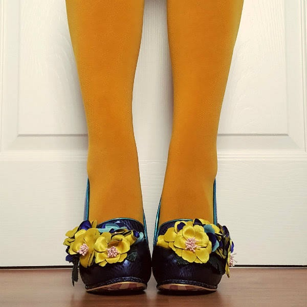 feet facing forward with yellow tights and blue shoes with large flowers on them