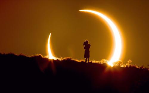 Eclipse solar, em forma de anel, ao fundo de uma paisagem em que um homem está de pé em um morro